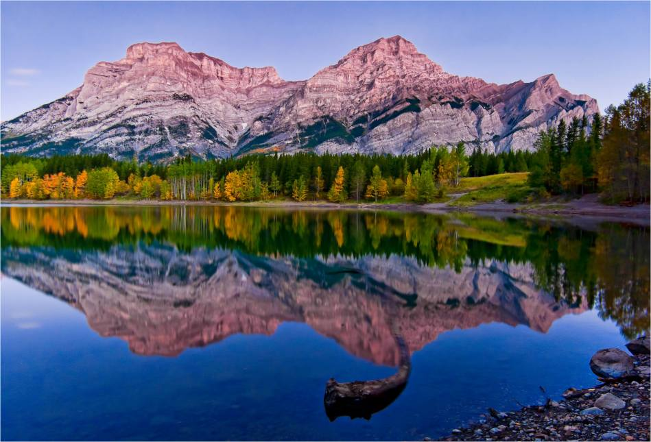 Mount Kidd glows in the early light of a fall morning at Wedge Pond in Kananaskis, Alberta in the Canadian Rocky Mountains.