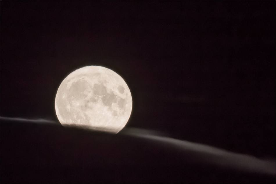 The full moon rolling down a hill of clouds. Photographed on September 1, 2020 west of Calgary, Alberta near Bragg Creek.