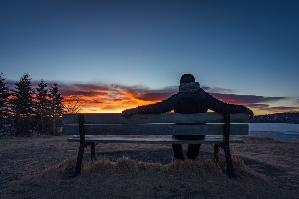 A man sitting on a park bench is silhouetted by a fiery cloud during sunrise at Ghost Lake, east of Cochrane, Alberta, Canada.  Photographed on March 20, 2021.